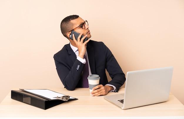 Uomo d'affari giovane nel suo ufficio con un computer portatile e altri documenti in possesso di caffè da portare via e un cellulare Foto Premium