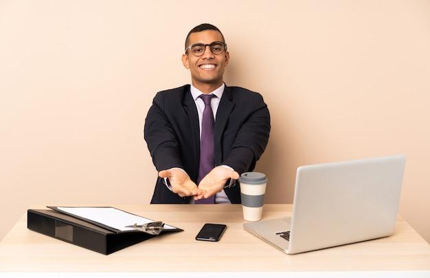 Uomo d'affari giovane nel suo ufficio con un computer portatile e altri documenti in possesso di copyspace immaginario sul palmo per inserire un annuncio Foto Premium