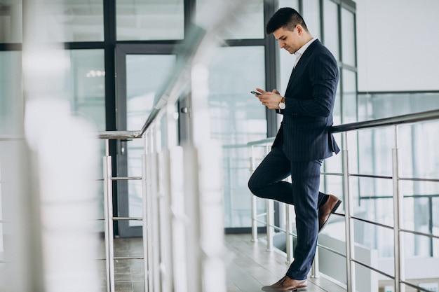 Uomo d'affari giovane parla al telefono in ufficio Foto Gratuite