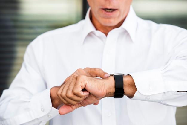 Uomo d'affari guardando orologio da polso Foto Gratuite