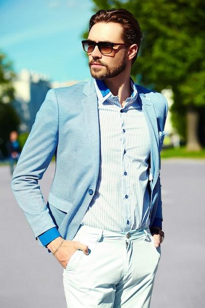 Uomo d'affari in abito blu indossando occhiali da sole in strada Foto Gratuite