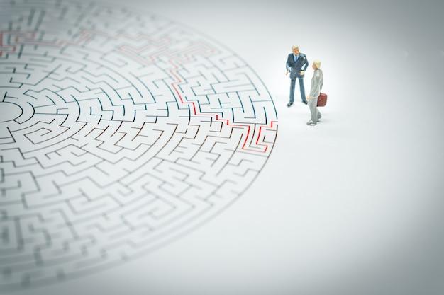 Uomo d'affari in miniatura camminando in un labirinto. Foto Premium