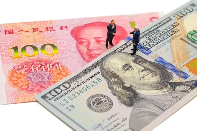 Uomo d'affari in miniatura con dollaro usa e banconota china yuan in riunione aziendale Foto Premium