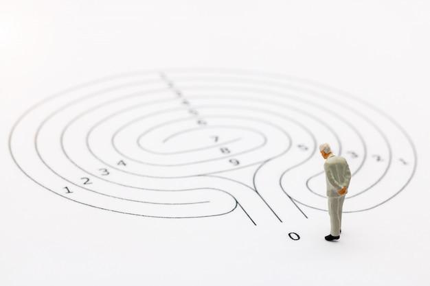 Uomo d'affari in piedi sul punto di partenza del labirinto e pensando a come risolvere questo problema. Foto Premium