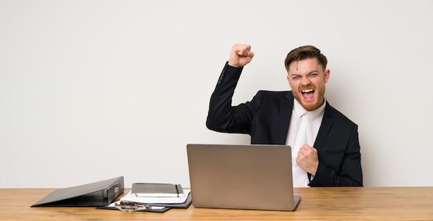 Uomo d'affari in un ufficio che celebra una vittoria Foto Premium