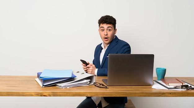 Uomo d'affari in un ufficio sorpreso e l'invio di un messaggio Foto Premium
