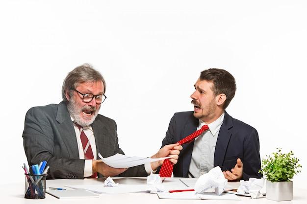 Uomo d'affari in un vestito che prende un dono all'ufficio sullo studio bianco Foto Gratuite