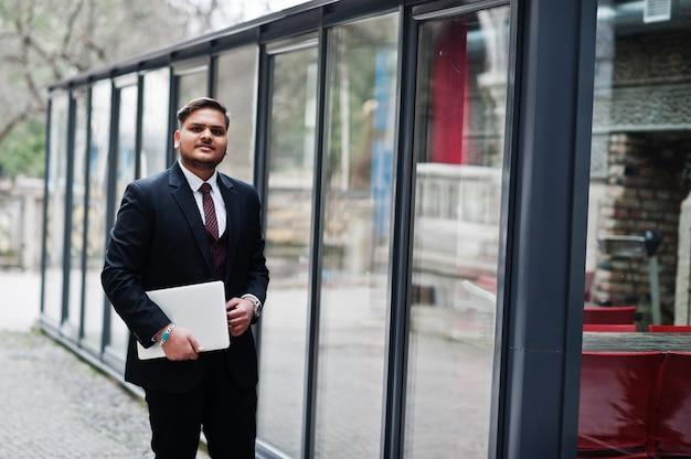 Uomo d'affari indiano alla moda nell'usura convenzionale con il computer portatile sulle mani che stanno contro le finestre nel centro di affari. Foto Premium