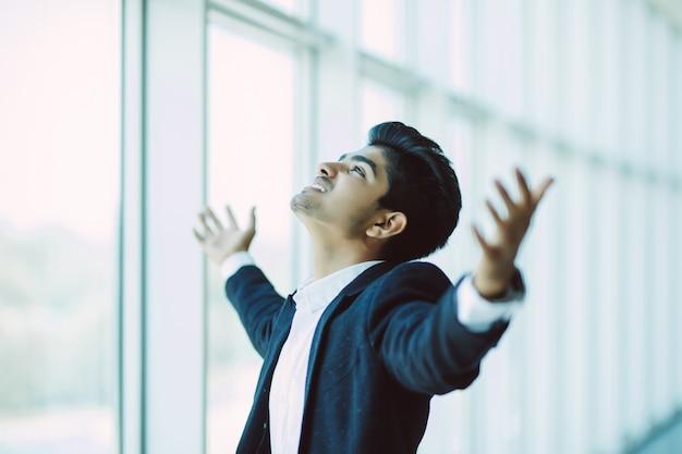 Uomo d'affari indiano bello felice nella regolazione moderna dell'ufficio che celebra le grandi notizie Foto Gratuite