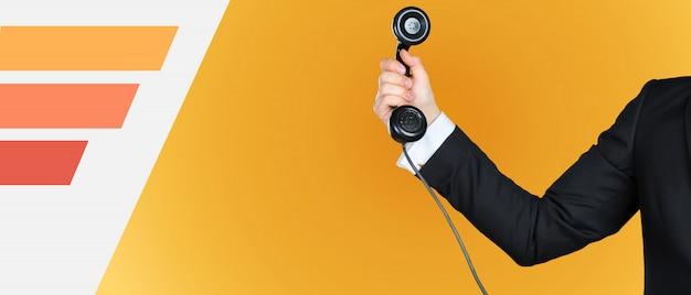 Uomo d'affari irriconoscibile che tiene un ricevitore telefonico d'annata Foto Premium
