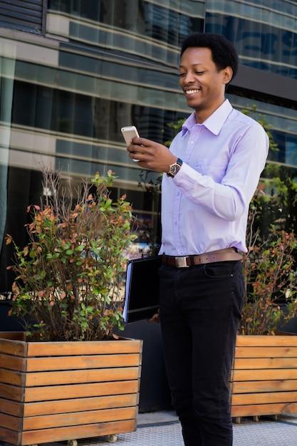 Uomo d'affari latino che utilizza telefono cellulare nella città Foto Premium