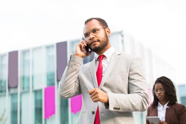 Uomo d'affari latino serio che parla sul cellulare Foto Gratuite