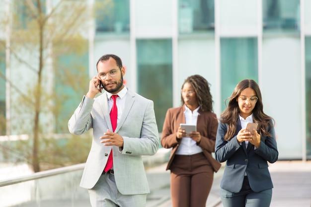 Uomo d'affari latino serio che parla sul telefono cellulare Foto Gratuite