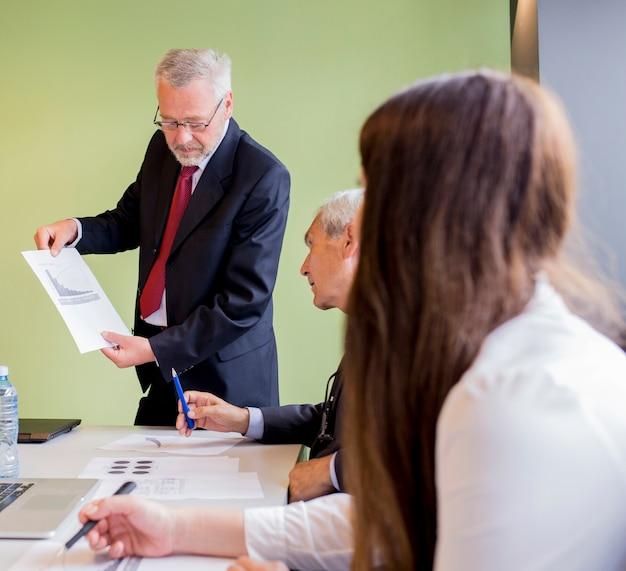 Uomo d'affari maturo che mostra grafico al suo socio commerciale nell'ufficio Foto Gratuite