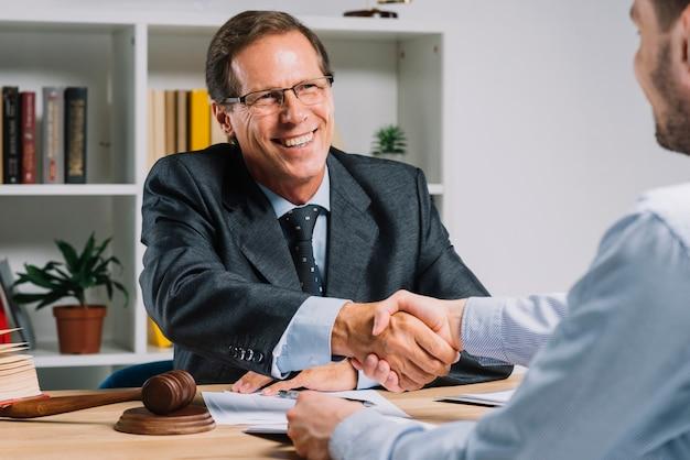 Uomo d'affari maturo sorridente che stringe le mani con il cliente nell'aula di tribunale Foto Gratuite