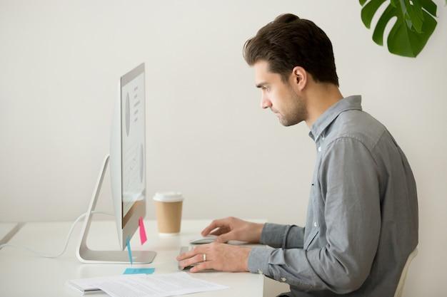 Uomo d'affari messo a fuoco che lavora al computer con le statistiche di progetto, vista laterale Foto Gratuite