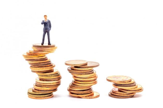 Uomo d'affari miniatura sulla pila sul mercato aziendale dell'incertezza bianca. Foto Premium