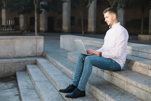 Uomo d'affari moderno che per mezzo del computer portatile all'aperto Foto Gratuite