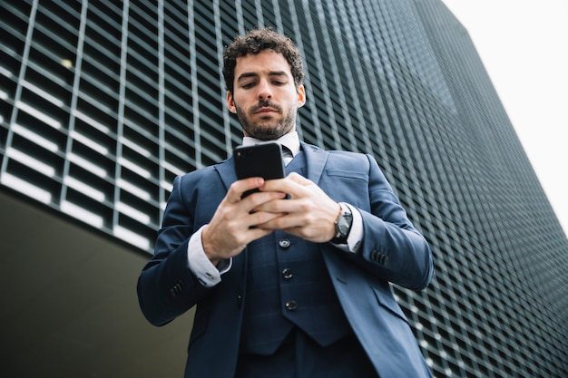 Uomo d'affari moderno usando smartphone all'aperto Foto Gratuite
