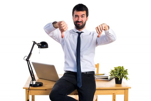 Uomo d'affari nel suo ufficio facendo cattivo segnale Foto Gratuite