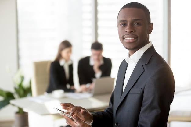 Uomo d'affari nero che utilizza compressa digitale sulla riunione Foto Gratuite