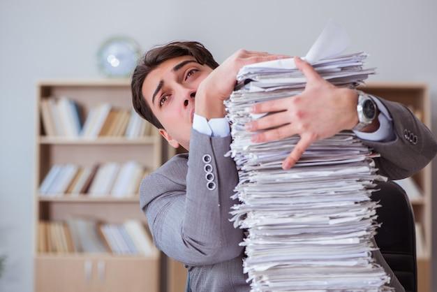 Uomo d'affari occupato con scartoffie in ufficio Foto Premium