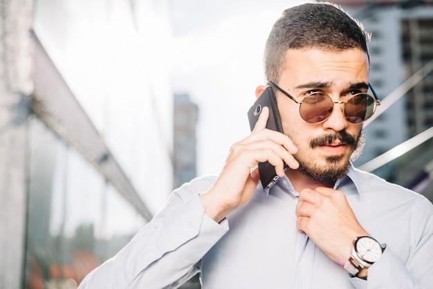 Uomo d'affari parlando al telefono e regolazione del colletto Foto Gratuite