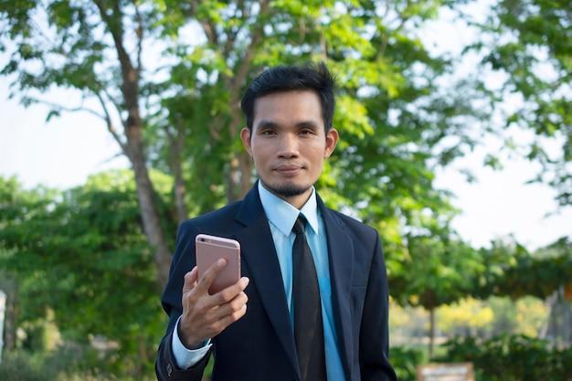 Uomo d'affari people che tiene smart phone mobile e telefono di conversazione Foto Premium