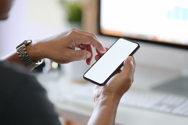 Uomo d'affari potato del colpo che per mezzo del telefono cellulare Foto Premium