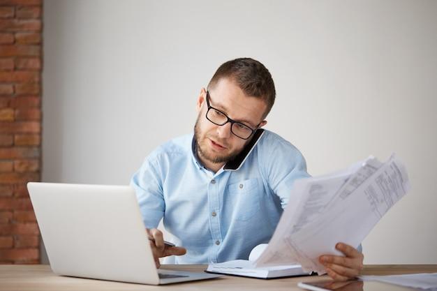 Uomo d'affari professionale serio che parla sul telefono con il cliente, tenendo le carte in mano Foto Gratuite