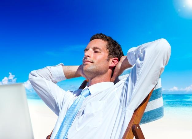 Uomo d'affari rilassante sulla spiaggia. Foto Gratuite