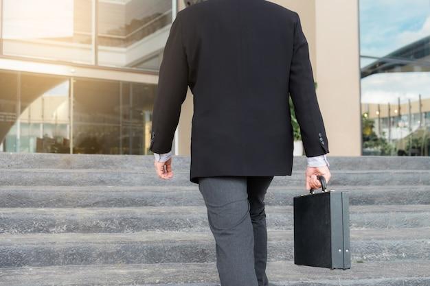 Uomo d'affari salendo le scale e tenendo in mano una valigetta lavorando con fiducia Foto Premium