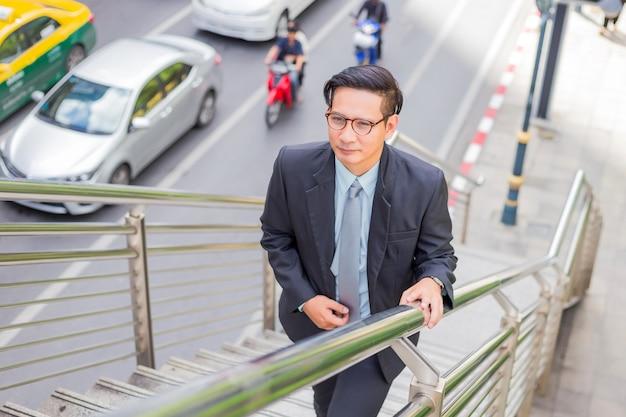 Uomo d'affari, salendo le scale in un'ora di punta per lavorare. Foto Premium