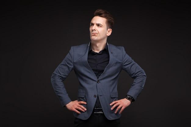 Uomo d'affari serio bello in giacca grigia, orologio costoso e camicia nera Foto Premium