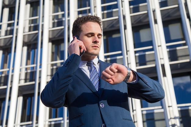 Uomo d'affari serio che controlla tempo che parla sul telefono. Foto Premium