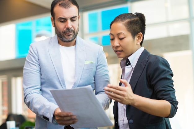 Uomo d'affari serio che discute documento alla donna di affari asiatica Foto Gratuite