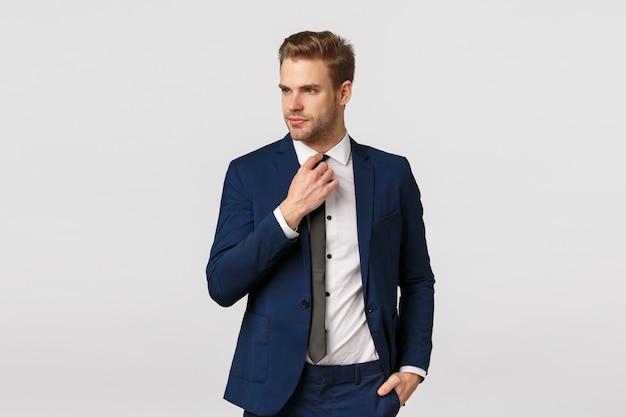 Uomo d'affari sfacciato serio in abito blu di classe, aggiustando la cravatta e guardando lontano, tenendosi per mano in tasca, preparandosi per il lavoro, aspettando un taxi in centro per andare incontro di lavoro, salutare i partner Foto Premium