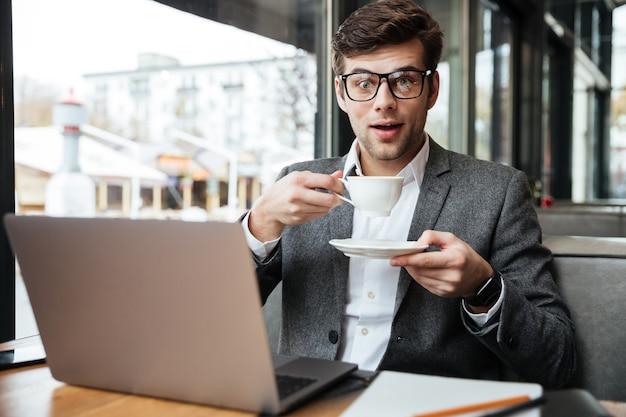 Uomo d'affari sorpreso in occhiali che si siedono dalla tavola in caffè con il computer portatile mentre tenendo tazza di caffè e sguardo Foto Gratuite