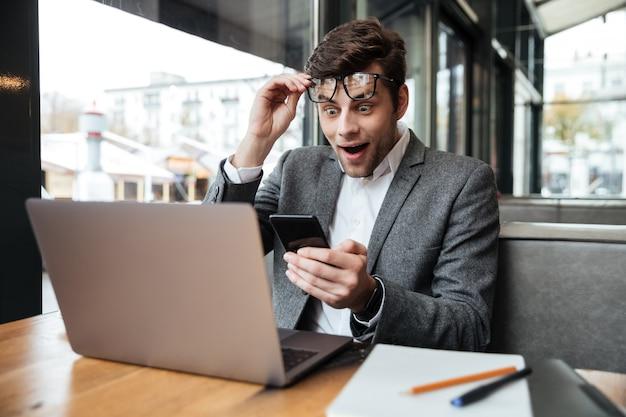 Uomo d'affari sorpreso in occhiali che si siedono dalla tavola in caffè mentre tengono smartphone e guardando il computer portatile Foto Gratuite