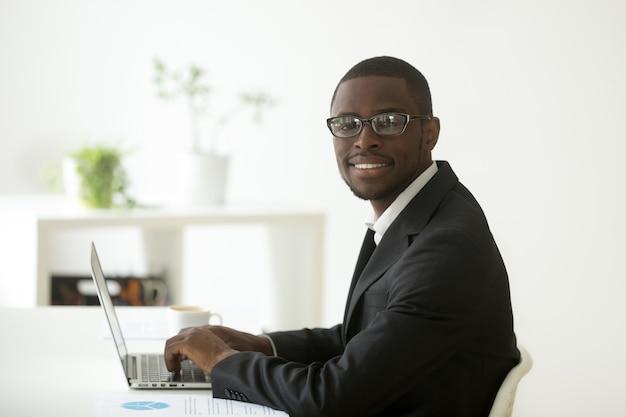 Uomo d'affari sorridente afroamericano in vestito e vetri che esaminano macchina fotografica Foto Gratuite