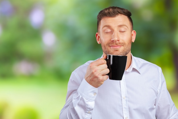 Uomo d'affari sorridente bello holding cup Foto Premium
