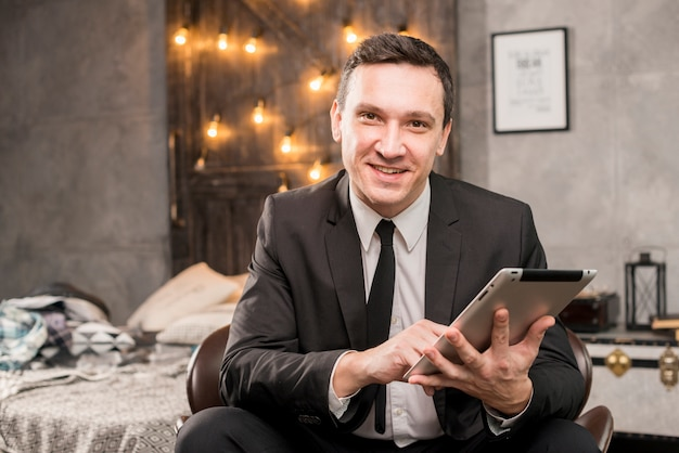 Uomo d'affari sorridente che lavora al tablet Foto Gratuite