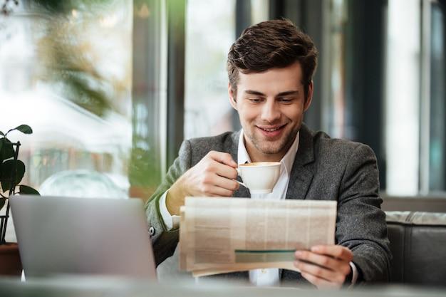 Uomo d'affari sorridente che si siede dalla tavola in caffè con il computer portatile mentre leggendo giornale e bevendo caffè Foto Gratuite