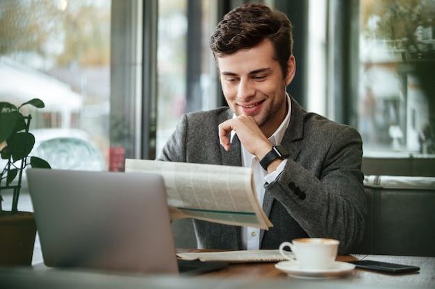 Uomo d'affari sorridente che si siede dalla tavola in caffè con il computer portatile mentre leggendo giornale Foto Gratuite