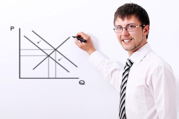 Uomo d'affari sorridente che traccia il grafico di domanda e offerta Foto Gratuite