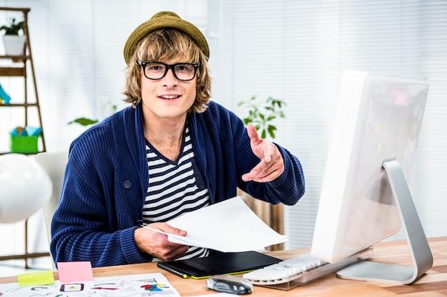 Uomo d'affari sorridente dei pantaloni a vita bassa che lavora al suo scrittorio Foto Premium