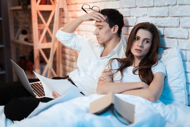 Uomo d'affari stanco che si siede a letto lavorando al computer portatile Foto Premium