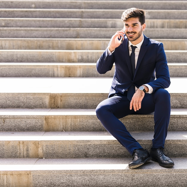 Uomo d'affari sul cellulare Foto Gratuite