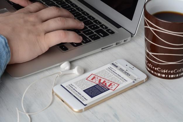 Uomo d'affari sulla tastiera con la tazza di caffè e notizie false digitali sullo smartphone Foto Premium