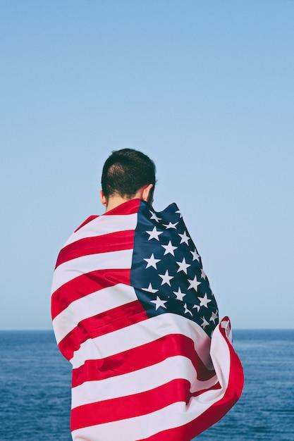 Uomo da dietro avvolto nella bandiera americana Foto Premium